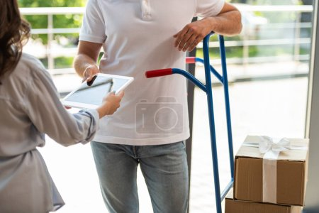 Photo pour Vue recadrée du livreur debout près du chariot de livraison avec boîtes et femme avec tablette numérique - image libre de droit