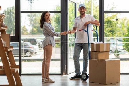 Photo for Selective focus of delivery man standing near delivery cart with boxes and woman with digital tablet - Royalty Free Image