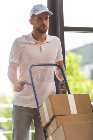 Photo for Handsome delivery man in cap holding delivery cart with cardboard boxes - Royalty Free Image