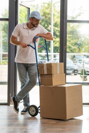 Photo pour Beau livreur dans le chapeau restant près du chariot de livraison et regardant les boîtes en carton - image libre de droit