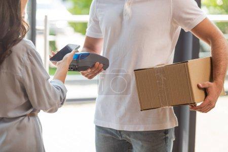 Photo pour Vue recadrée du livreur retenant le terminal de paiement près de la femme payant avec le smartphone - image libre de droit