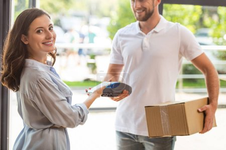Photo for Selective focus of happy woman paying while holding smartphone near credit card reader in hand on delivery man - Royalty Free Image