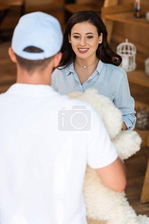 Photo pour Vue arrière de l'homme de livraison retenant l'ours de nounours près de la femme attirante - image libre de droit