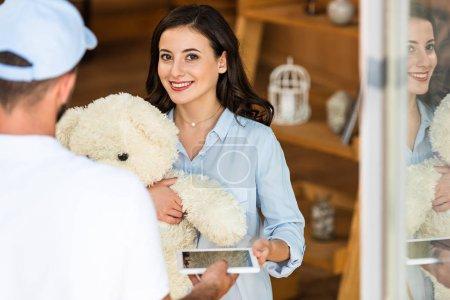 Photo pour Vue arrière de l'homme de livraison donnant la tablette numérique à la femme heureuse avec l'ours de nounours - image libre de droit