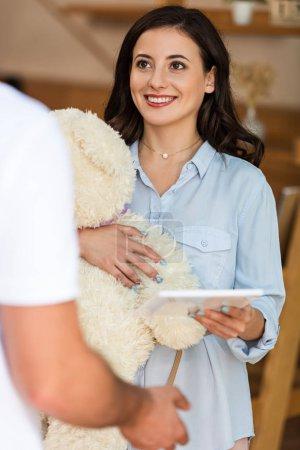 Foto de Vista recortada del repartidor cerca de la mujer feliz con oso de peluche y tableta digital - Imagen libre de derechos