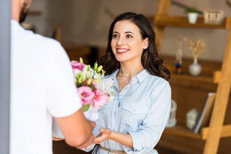 Photo pour Vue recadrée de livraison homme donnant des fleurs à femme heureuse - image libre de droit