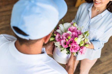 Photo pour Vue aérienne de livraison homme donnant des fleurs à femme gaie - image libre de droit