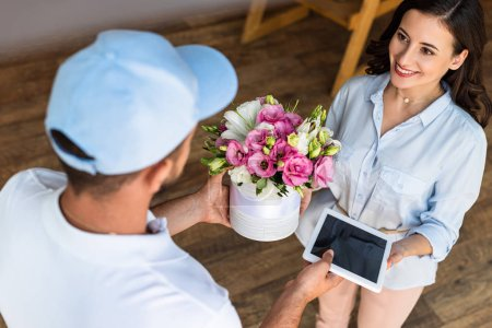 Photo for Overhead view of delivery man giving flowers and digital tablet with blank screen to cheerful woman - Royalty Free Image