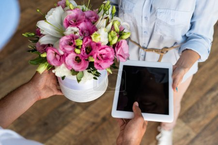 Photo for Overhead view of delivery man giving flowers and digital tablet with blank screen to  woman - Royalty Free Image