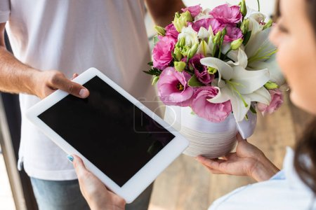 Photo pour Vue recadrée de livreur donnant des fleurs et la tablette numérique avec l'écran blanc à la femme - image libre de droit