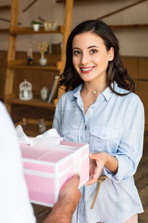 Photo for Selective focus of cheerful girl receiving present from delivery man - Royalty Free Image