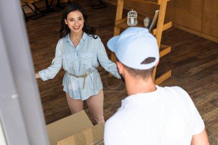 Foto de Enfoque selectivo de la mujer feliz mirando al repartidor en gorra blanca - Imagen libre de derechos