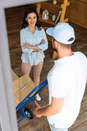 Photo pour Foyer sélectif de la femme heureuse avec les bras croisés regardant l'homme de livraison dans le chapeau marchant avec le chariot de livraison - image libre de droit