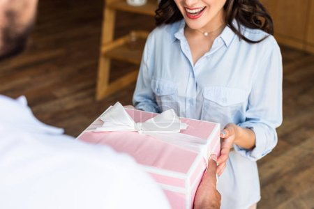 Foto de Vista recortada de la mujer feliz recibiendo regalo del repartidor - Imagen libre de derechos