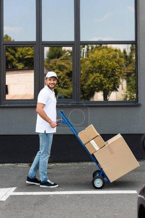 Photo pour Homme barbu heureux de livraison restant avec le chariot de livraison près du bâtiment - image libre de droit