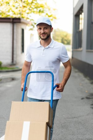 Photo for Positive delivery man standing with delivery cart near building - Royalty Free Image