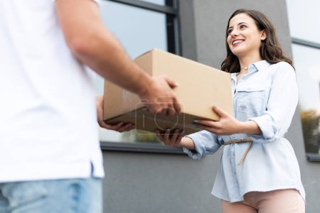 cropped view of delivery man giving box to happy woman outside