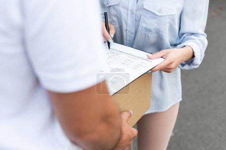 Photo pour Vue recadrée de l'homme de livraison retenant la boîte près du stylo de fixation de fille près du presse-papiers à l'extérieur - image libre de droit