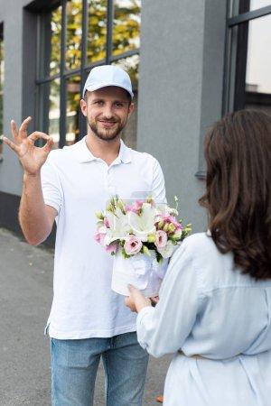 Photo pour Foyer sélectif de livraison heureux homme en chapeau montrant ok signe près de la femme avec des fleurs - image libre de droit