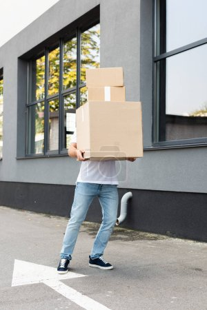 Photo for Delivery man covering face while holding packages near building - Royalty Free Image