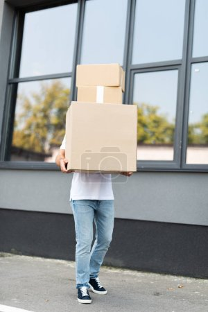 Photo for Delivery man covering face while holding boxes near building - Royalty Free Image