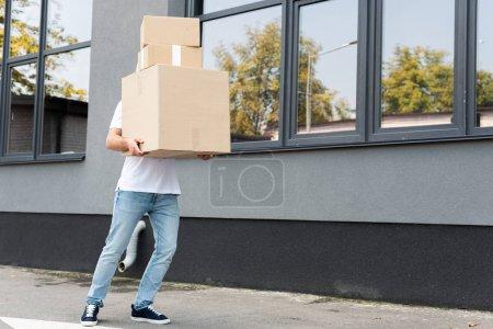 Photo pour Livreur en jean bleu denim couvrant le visage tout en tenant des boîtes près du bâtiment - image libre de droit