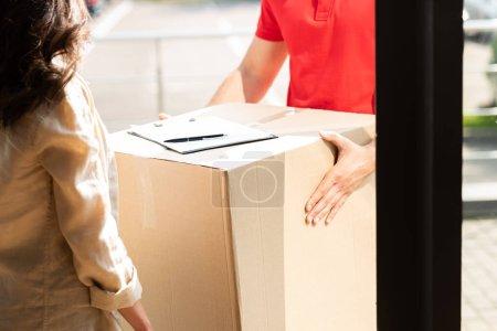 Photo pour Vue recadrée de l'homme de livraison retenant la boîte près de la femme - image libre de droit