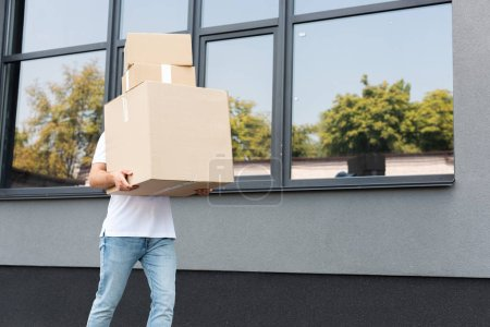 Photo for Delivery man in denim blue jeans holding boxes near building - Royalty Free Image