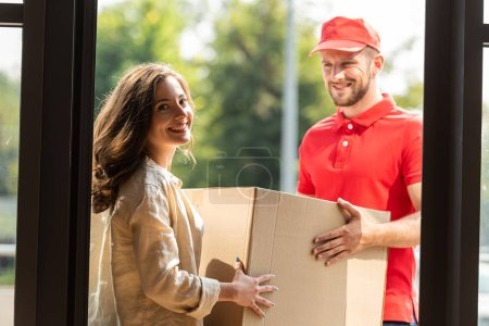 Photo for Cheerful delivery man in cap looking at camera and holding box near woman - Royalty Free Image