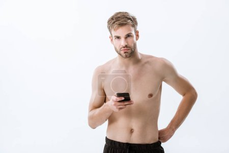 Photo for Bearded shirtless sportsman looking at camera and holding smartphone isolated on grey - Royalty Free Image