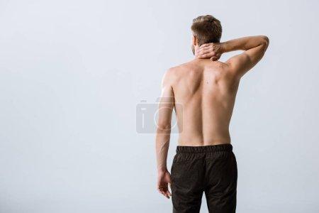 Photo pour Vue arrière de l'homme torse nu avec la douleur de cou d'isolement sur le gris - image libre de droit