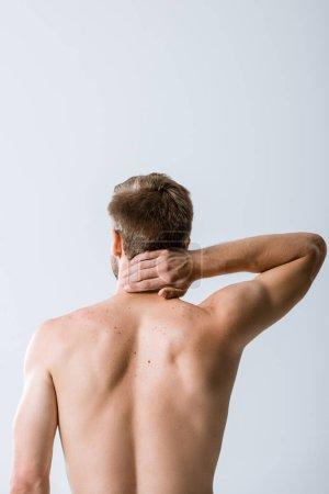 Foto de Vista trasera del hombre sin camisa con dolor de cuello aislado en gris - Imagen libre de derechos