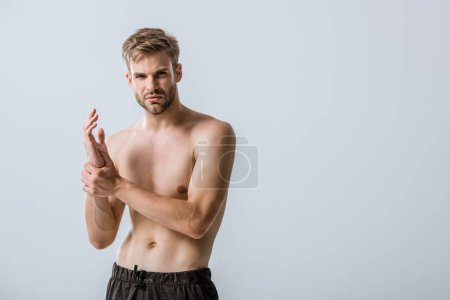Photo for Shirtless bearded man with wrist pain isolated on grey - Royalty Free Image