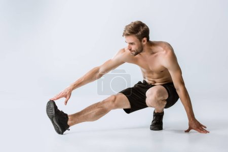 Photo for Shirtless bearded man in black sneakers stretching on grey - Royalty Free Image