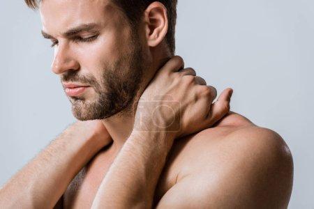 Hemdloser bärtiger Sportler mit Nackenschmerzen isoliert auf grau