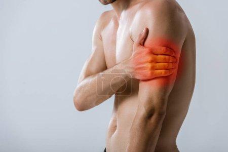 Photo pour Vue recadrée d'un sportif torse nu avec douleurs aux bras isolées sur fond gris - image libre de droit
