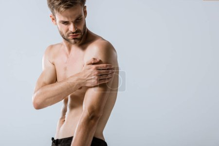 Photo for Shirtless bearded sportsman with arm pain isolated on grey - Royalty Free Image