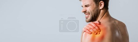 Photo for Panoramic shot of shirtless sportsman with shoulder pain isolated on grey - Royalty Free Image