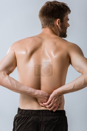Photo for Back view of shirtless sportsman with lower back pain isolated on grey - Royalty Free Image