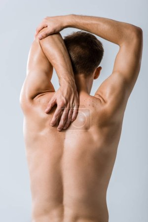 Photo for Back view of shirtless sportsman stretching isolated on grey - Royalty Free Image
