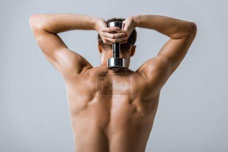 Photo pour Vue arrière d'un sportif torse nu utilisant un haltère isolé sur fond gris - image libre de droit