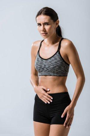 Photo pour Attrayant sportif avec des douleurs à l'estomac isolé sur gris - image libre de droit
