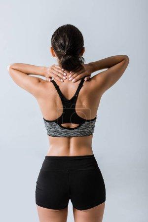Foto de Vista trasera de la deportista con dolor de cuello aislado en gris - Imagen libre de derechos