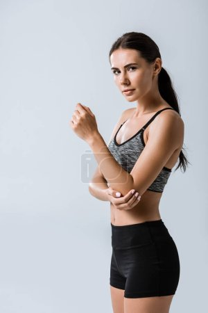 Photo for Attractive sportswoman with elbow pain isolated on grey - Royalty Free Image