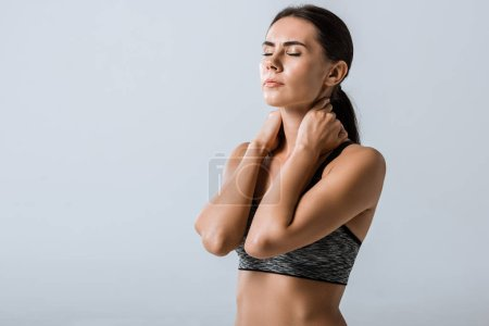Photo for Attractive sportswoman with neck pain isolated on grey - Royalty Free Image