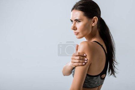 Photo pour Attrayant sportif brune avec douleur au bras isolé sur gris - image libre de droit