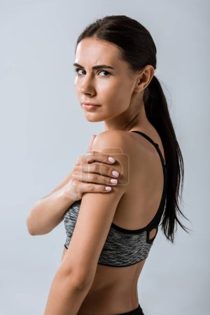 Photo for Attractive brunette sportswoman with arm pain isolated on grey - Royalty Free Image