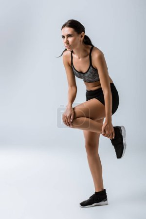 Photo for Full length view of sportswoman feeling knee pain while warming up on grey - Royalty Free Image