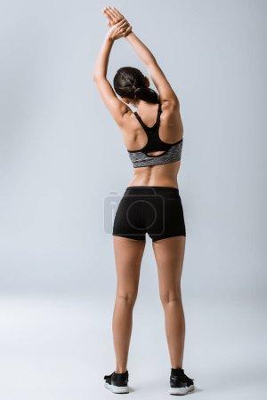 Foto de Vista posterior de la deportista sexy calentamiento en gris - Imagen libre de derechos