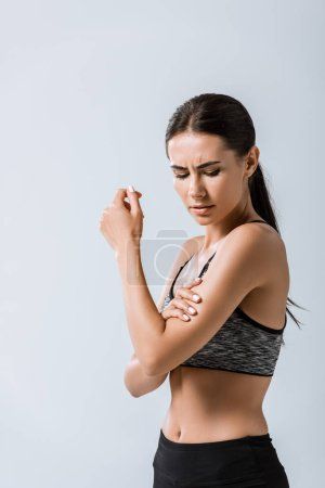 Photo for Attractive sportswoman with arm pain isolated on grey - Royalty Free Image